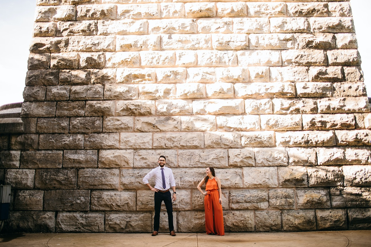 A couple poses against a brick wall, each with a hand on their hip.