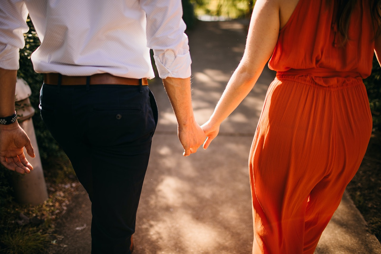 A close up image of a couple walking away from the camera hand-in-hand.
