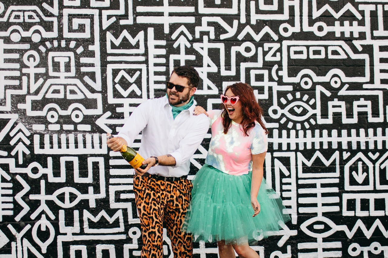 A couple in bright, funky clothes pops a bottle of champagne in front of a black and white geometric mural.