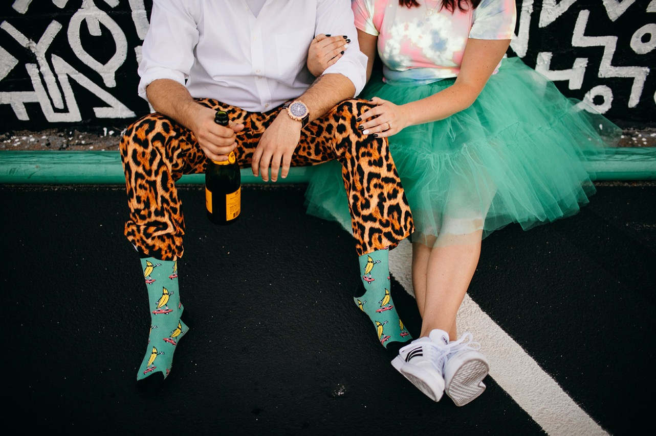 A close up of an engaged couple's lets while they sit against a black and white mural in downtown Chattanooga. He's wearing a white button-down, leopard pants, and teal socks with bananas on them. She's wearing a tie-die t-shirt, a teal tutu, and white Adidas sneakers.