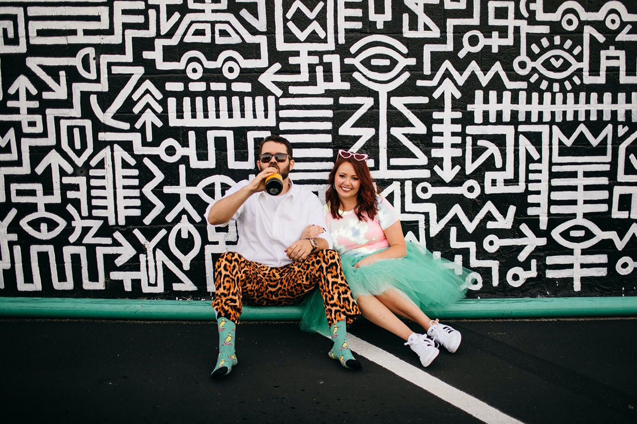 An engaged couple poses together sitting in front of a black and white mural in downtown Chattanooga.
