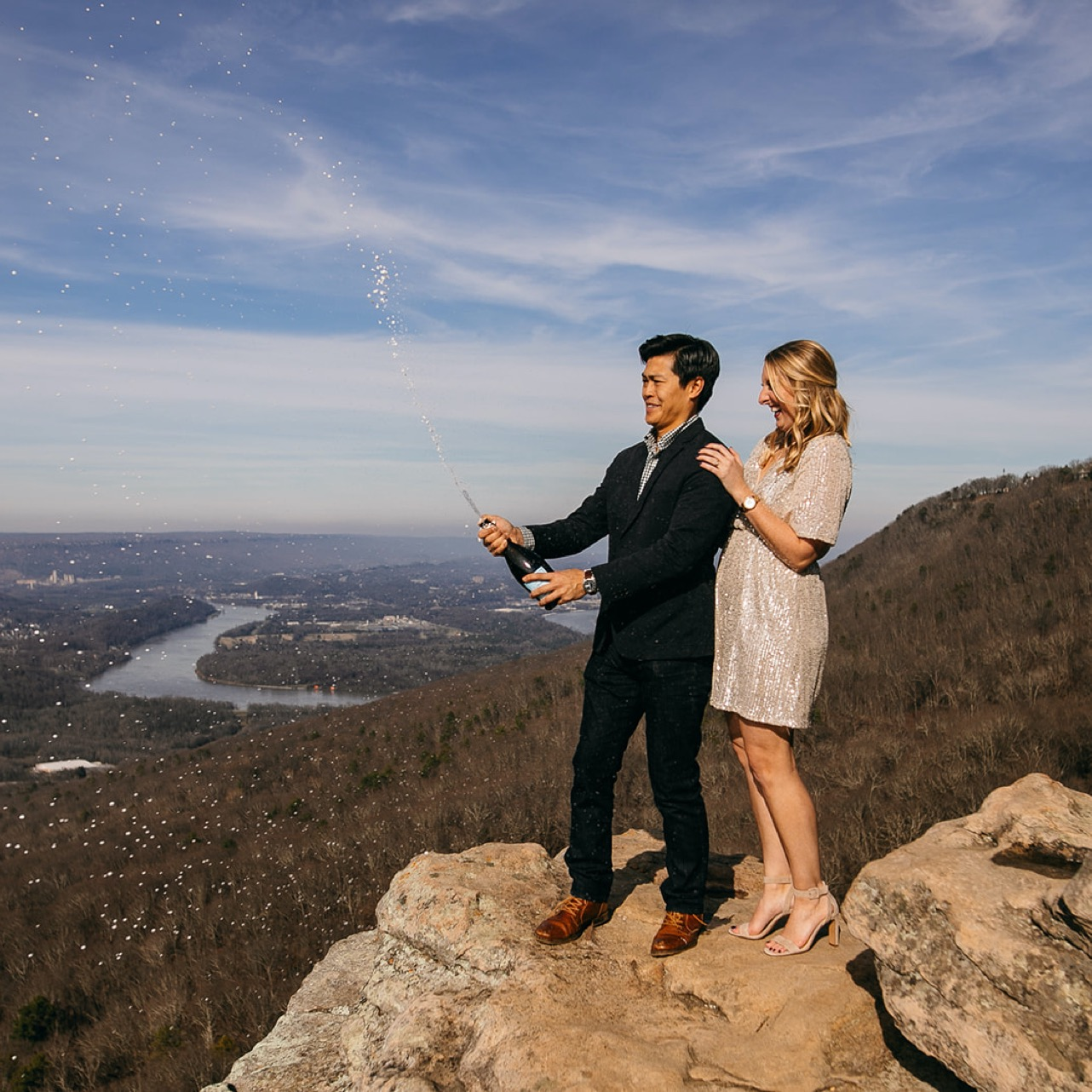 An engaged couple pops a bottle of champagne on top of Sunset Rock in Chattanooga.