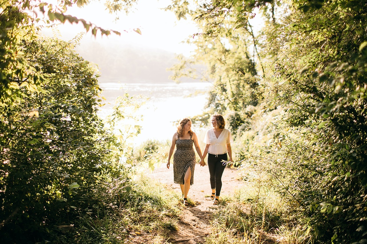 An engaged lesbian couple walks hand-in-hand through a sunny glade on the Tennessee River.