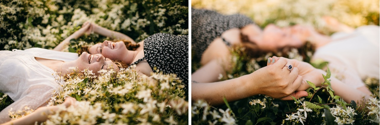 An engaged lesbian couple lays together in a field of wildflowers in Chattanooga.
