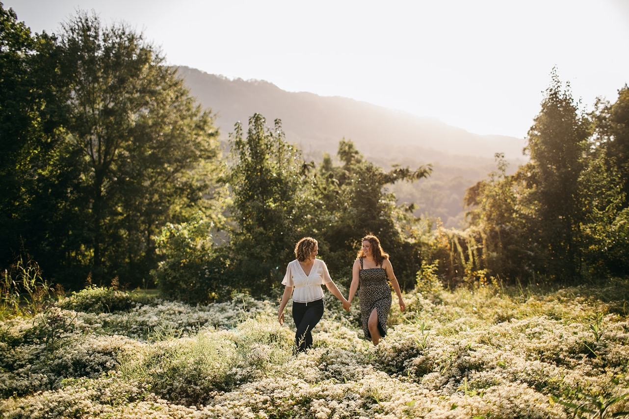 A lesbian couple walk hand-in-hand through a field of wildflowers near the Tennessee River.