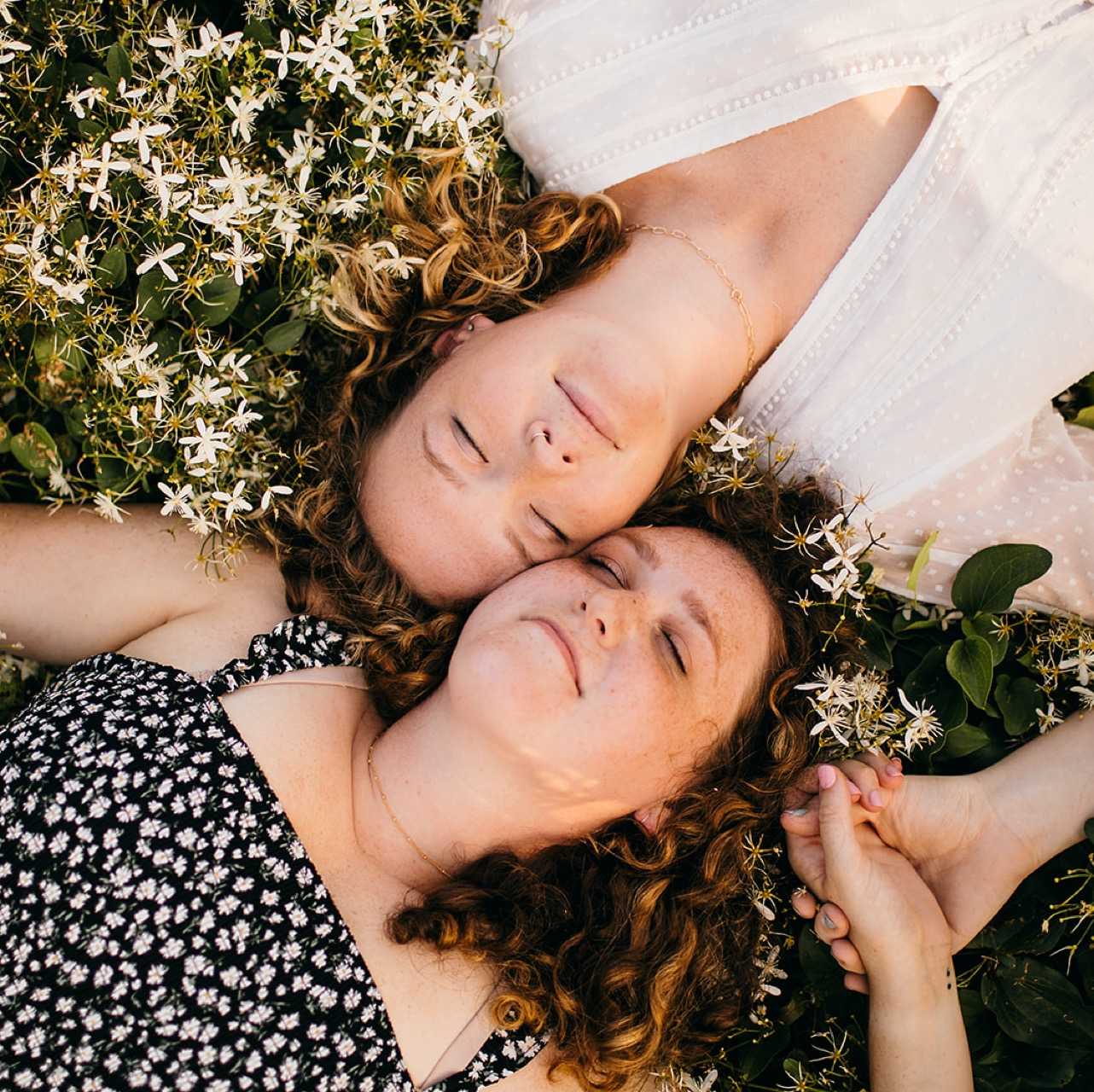 A lesbian couple lays in a field of white wildflowers with their heads against one another's. They're holding hands with their eyes closed.