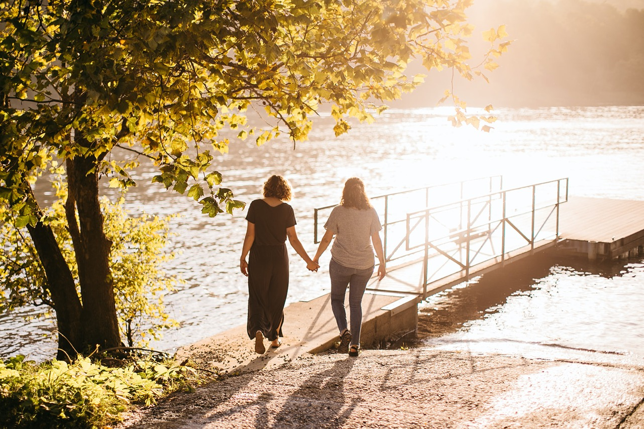 A lesbian couple walk hand-in-hand onto a dock on the Tennessee River at sunset.