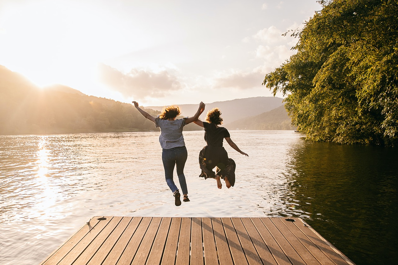 A lesbian couple jumps off a dock into the Tennessee River at sunset.