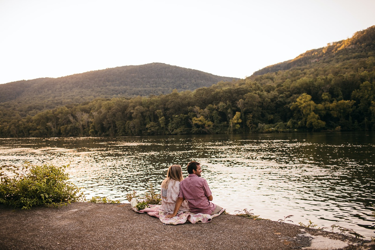 An engaged couple sits together looking out over the Tennessee River.