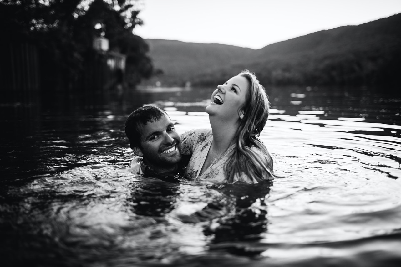 A black and white image of an engaged couple laughing while swimming in the Tennessee River.