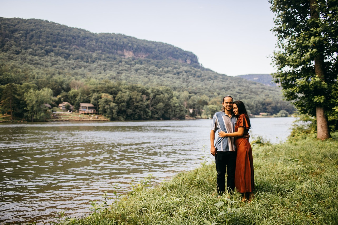 A man and woman stand embracing along the Tennessee River.