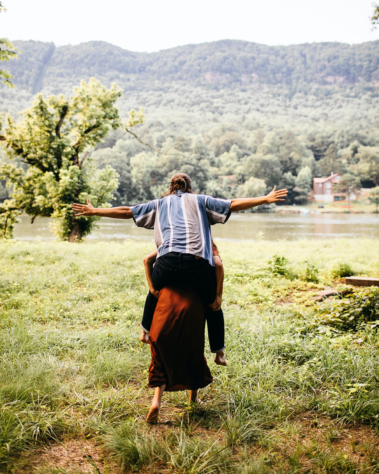 A woman gives her fiance a piggy back ride on the banks of the Tennessee River.