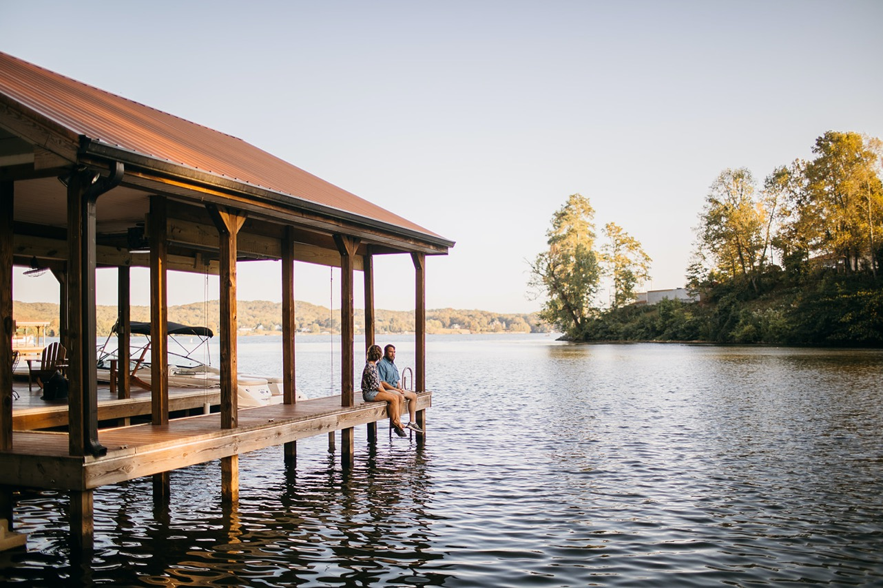 A couple sit together on a dock overlooking the Tennessee River during golden hour.