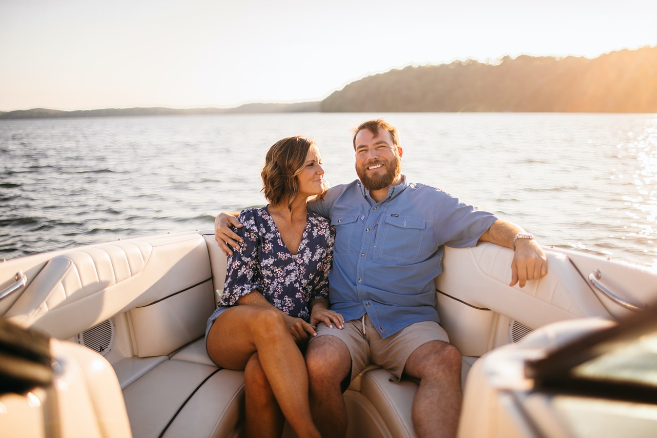 A man wraps his arm around his fiance and smiles for the camera as they sit on a boat on the Tennessee River.