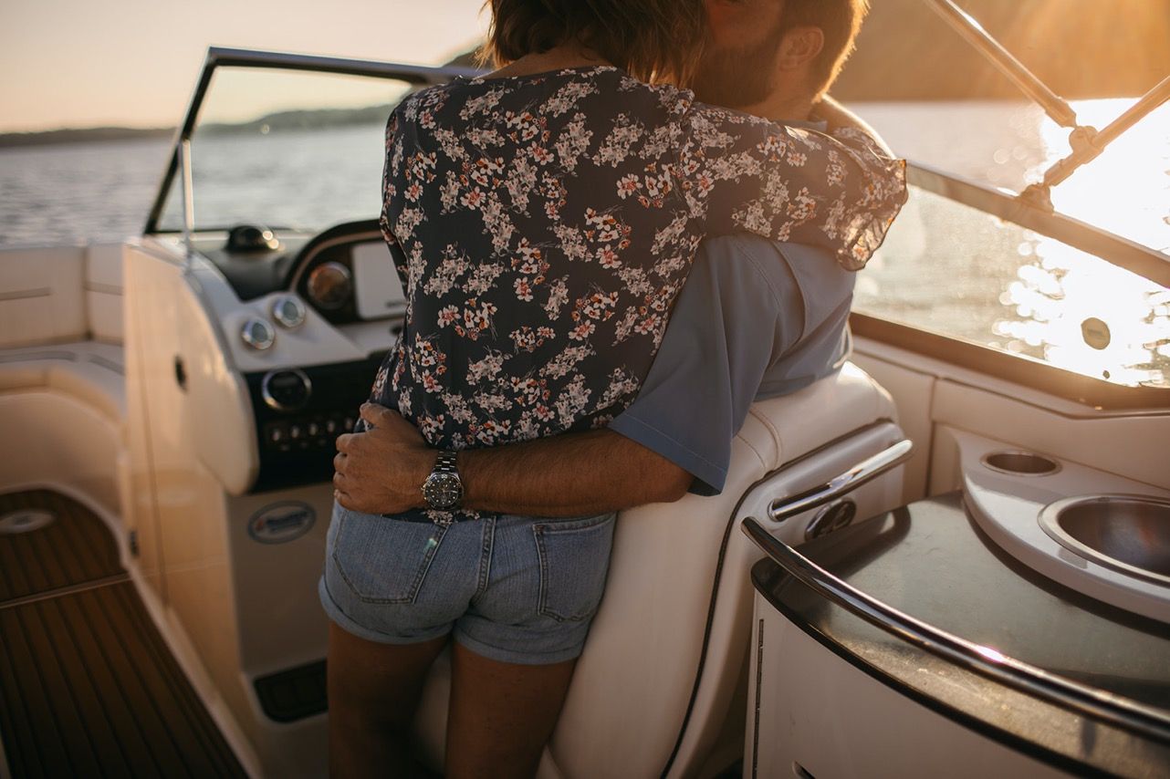 A photo from behind a man and woman embracing and kissing on a boat at sunset.