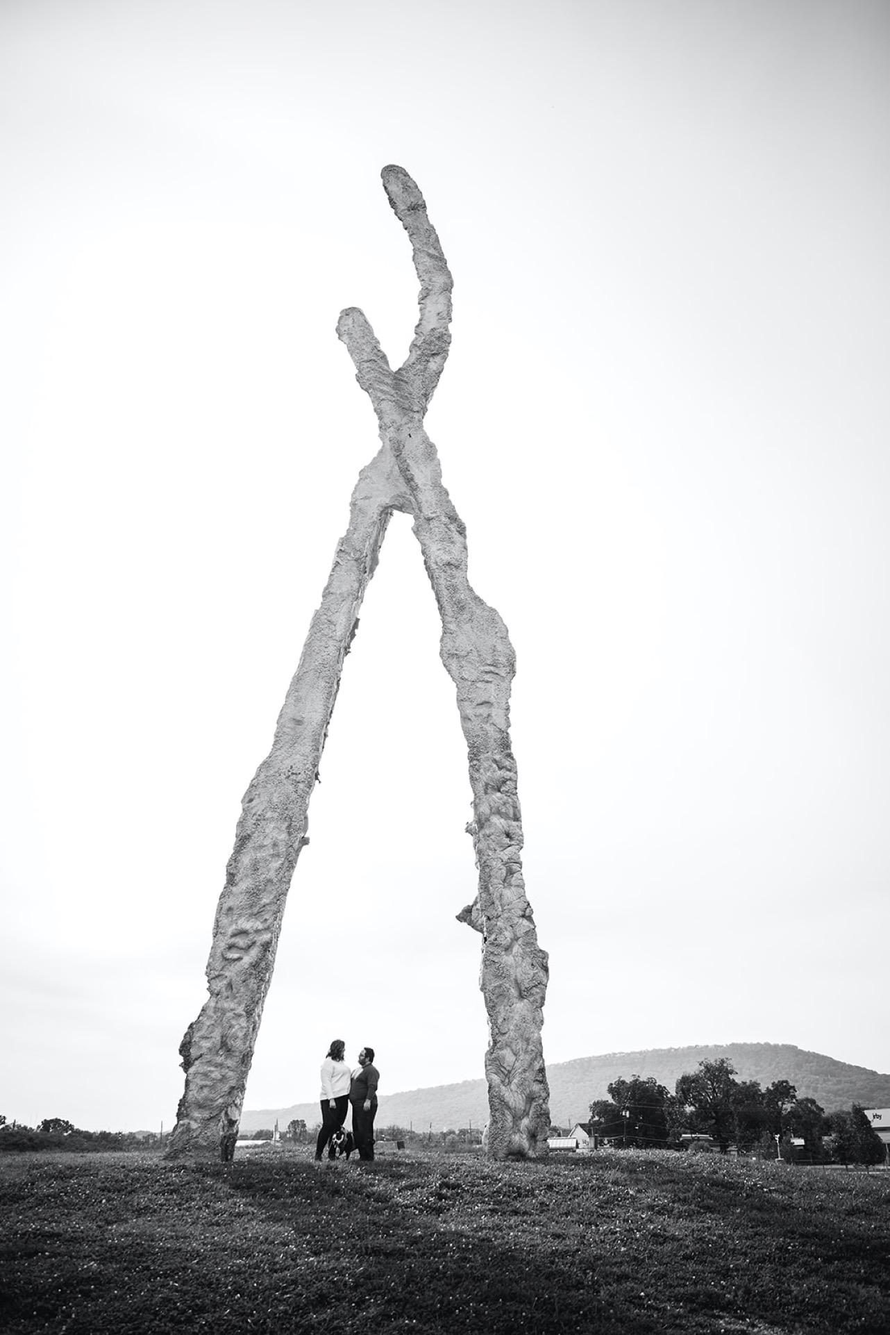 An engaged couple standing arm-in-arm beneath a massive sculpture in a park.