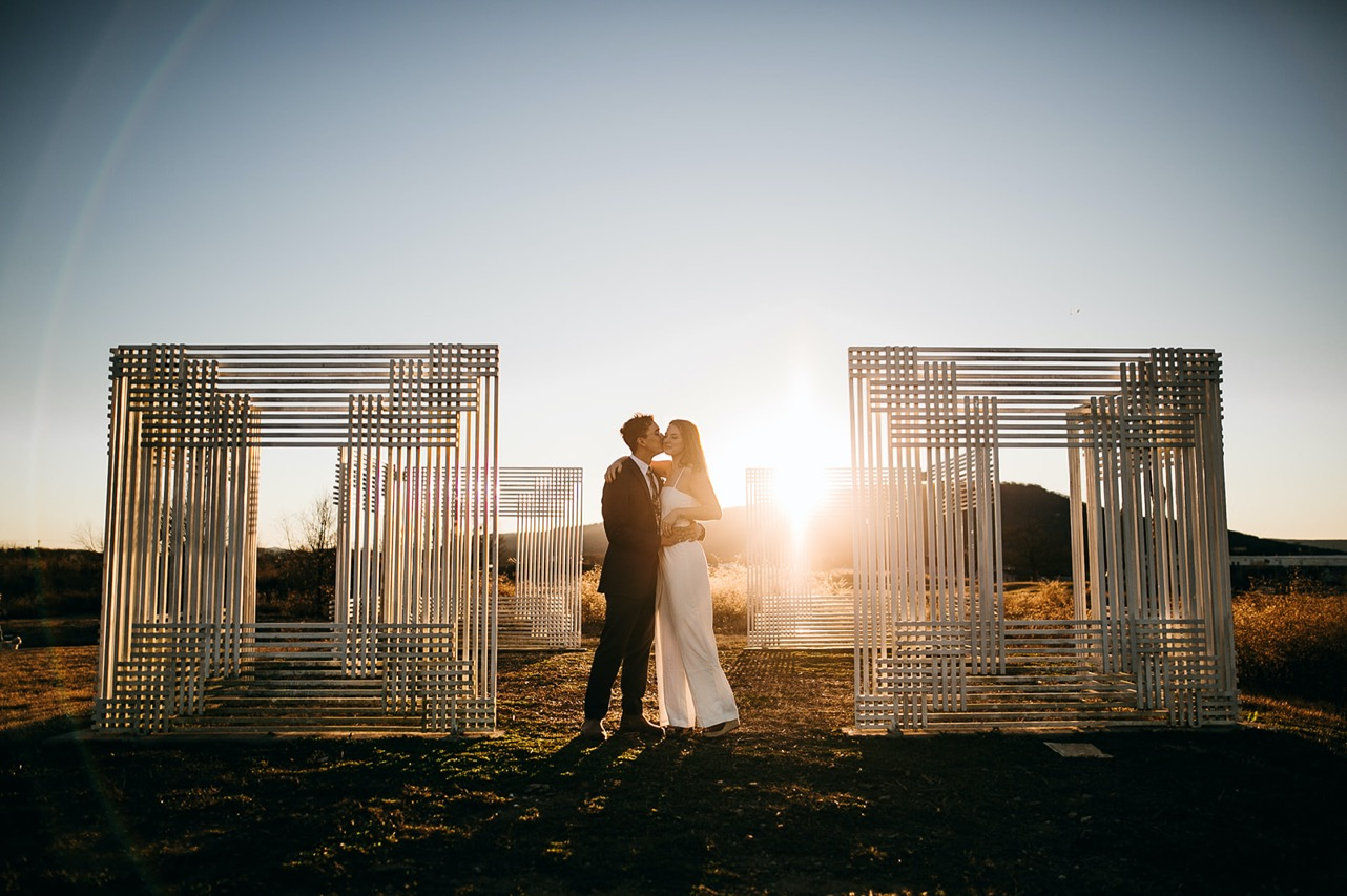 A couple kiss between two white, grid-like sculptures in the Chattanooga Sculpture Fields.