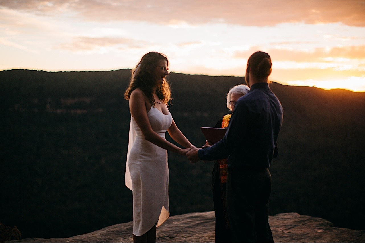 bride laughs at groom during their sunrise elopement ceremony
