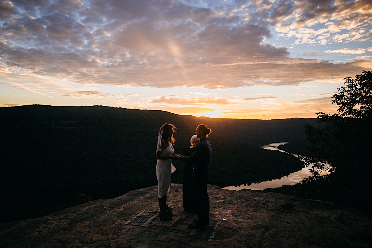 bride and groom look at each other as the sun rises during their elopement ceremony
