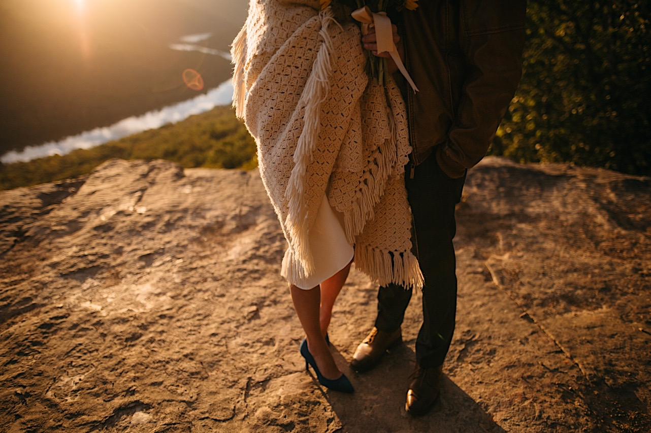 bride wraps up in a blanket next to her groom at their sunrise elopement