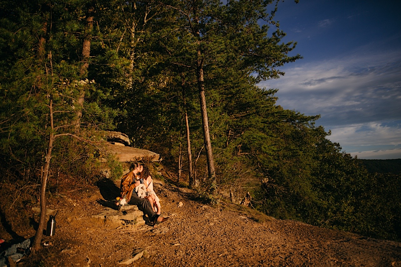 bride and groom sit on a rock and kiss at their Snooper's Rock elopement