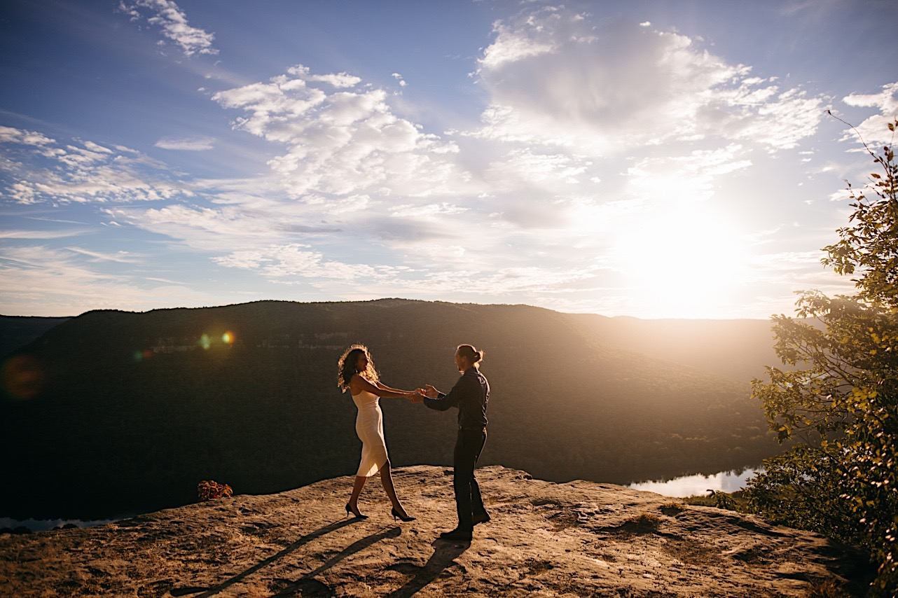 bride and groom dance on a cliff during the sunrise at their elopement