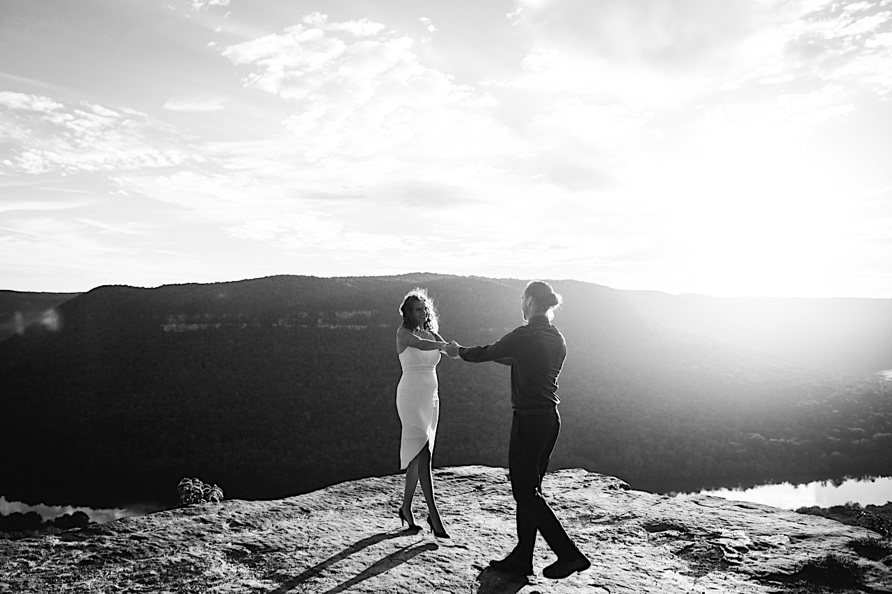 bride and groom dance on a cliff at their sunrise elopement