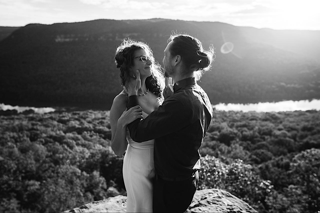 groom holds brides face as she smiles at their sunrise elopement