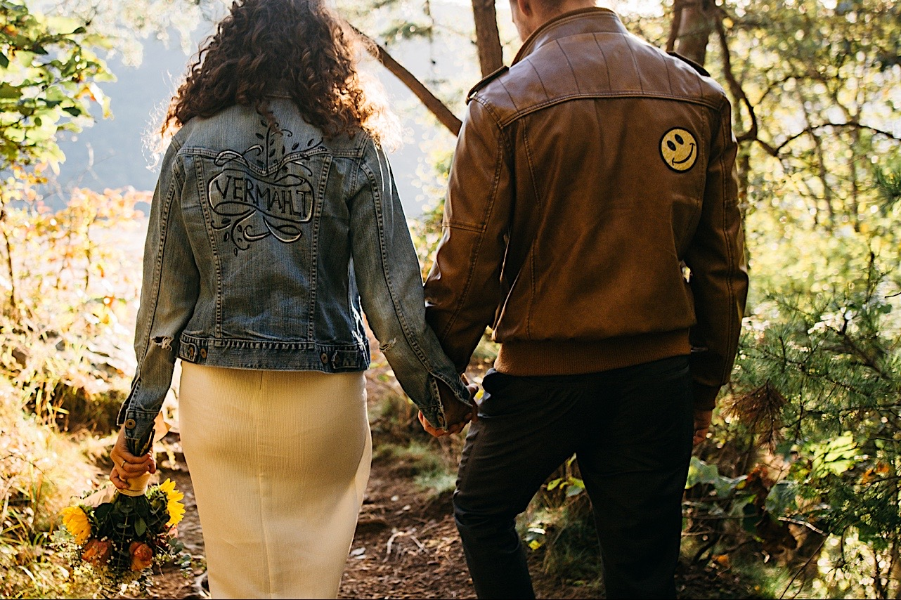 bride and groom hold hands as they walk through the forest at their Snooper's Rock elopement
