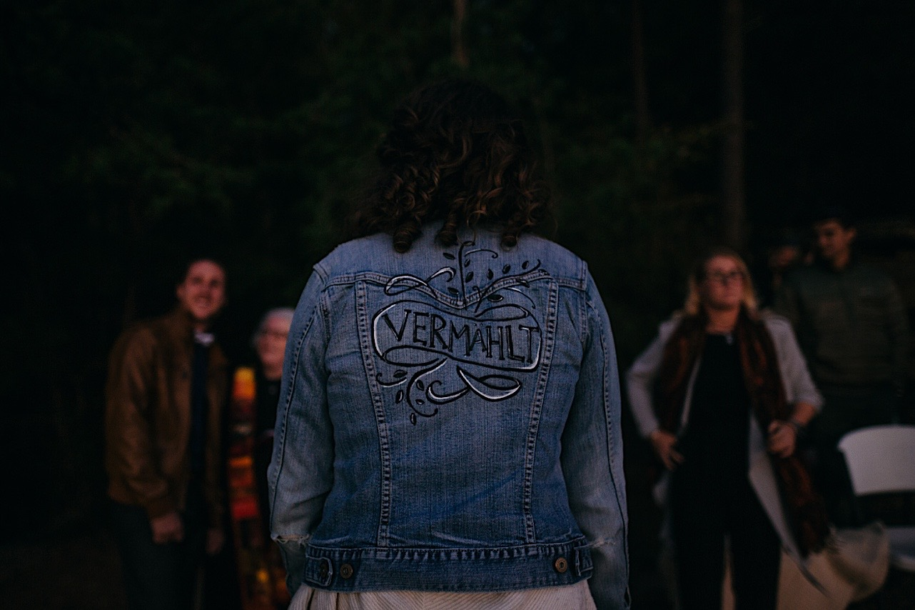bride shows off painted denim jacket during her sunrise elopement at Snooper's Rock